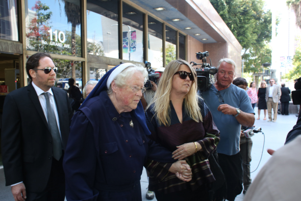 Sister Rita Callanan, center, is escorted by businesswoman Dana Hollister out of Los Angeles Superior Court on Thursday, July 30, 2015. Callanan is part of an order of elderly nuns locked in a battle with Los Angeles' archbishop over the sale of their former convent, which pop singer Katy Perry wants to buy.  (AP Photo/Anthony McCartney)