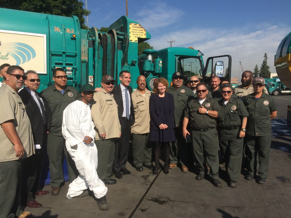Los Angeles Mayor Eric Garcetti (center) poses with  Bureau of Sanitation workers to celebrate the unveiling of newly designed sidewalk trash cans.