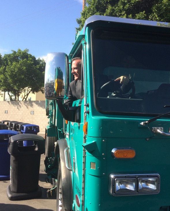 Los Angeles Mayor Eric Garcetti in a sanitation truck, giving the city's new sidewalk trash bins a whirl.